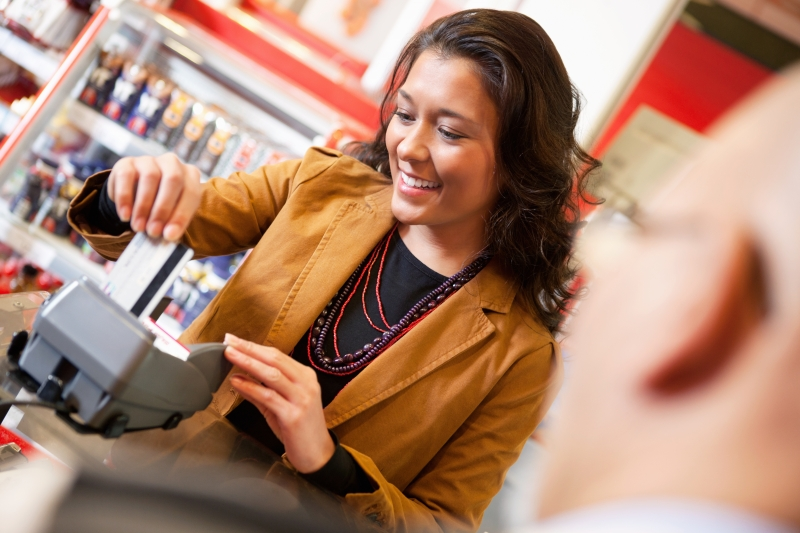 1794341-shop-assistant-smiling-while-swiping-credit-card-in-supermarket